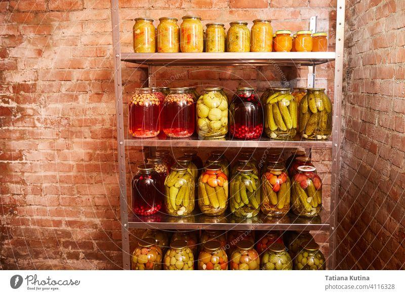 Lagerung von Gemüse und Obst für den Winter. Regal mit Banken mit Rohlingen in der Heimat Keller. Hintergrund Konservenherstellung Lebensmittel Glas