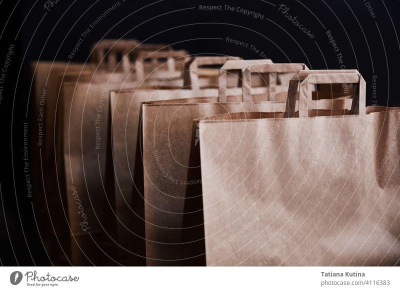 Braune Papiertüten auf einem schwarzen Hintergrund keine Verschwendung Paket Kauf mehrere kaufen Einzelhandel braun führen leer Tasche Menschengruppe weiß