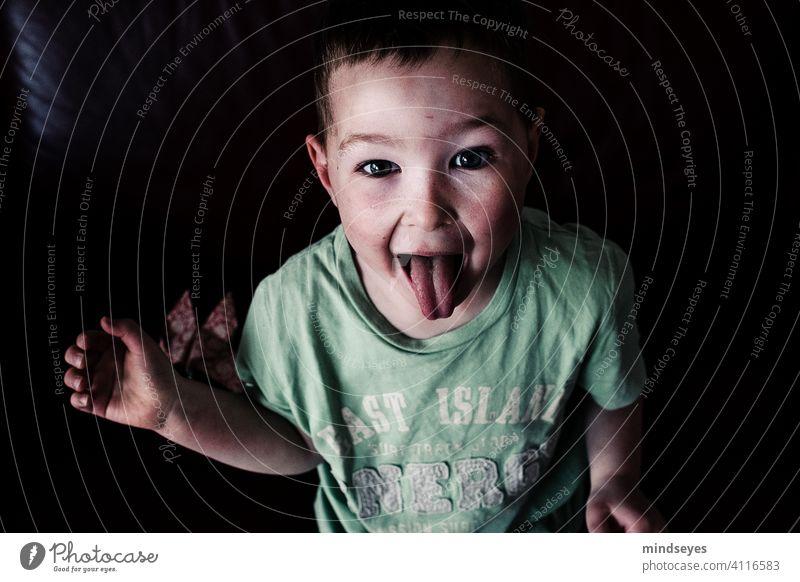 Frecher Junge Kindheit frech Zunge rausstrecken zunge zeigen Porträt lustig Gesicht Grimasse Blick in die Kamera Fröhlichkeit wild