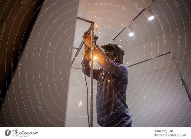 Arbeiter schweißt eine Umkleidekabine bei einer Hausrenovierung Business Konstruktion Maschinenbau Gerät Fabrik blitzen industriell Industrie Job Mann