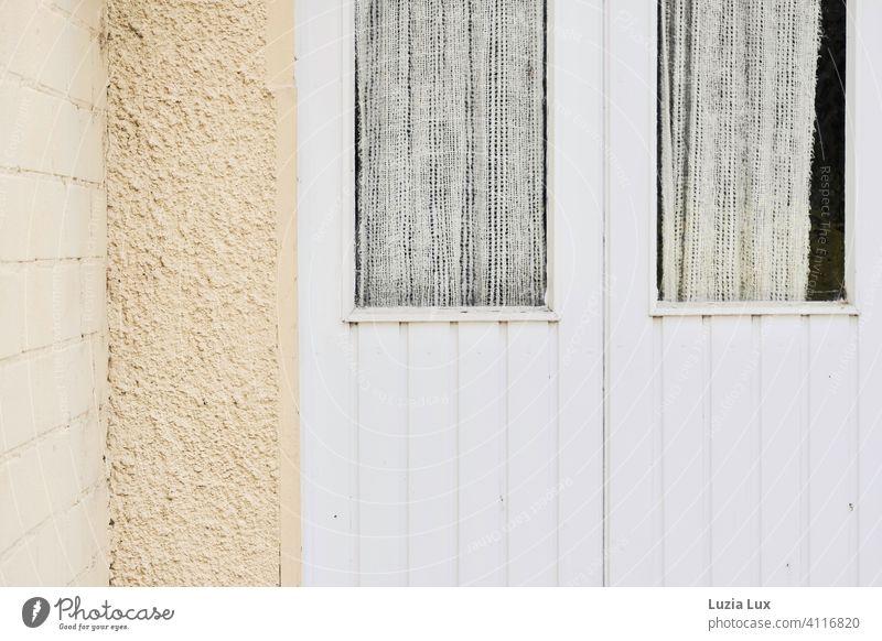 Eine alte Hintertür in zarten Farben, Fenster mit Gardine gelb beige weiß Holz Mauer Menschenleer Außenaufnahme Häusliches Leben Tag Vorhang Licht Sonnenlicht