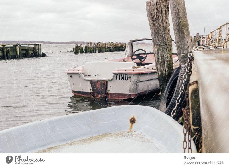 Alte verwitterte Boote an einem Holzsteg vertäut Steg Schifffahrt Wasser Meer Außenaufnahme Wasserfahrzeug Farbfoto Hafen Sommer Himmel Menschenleer