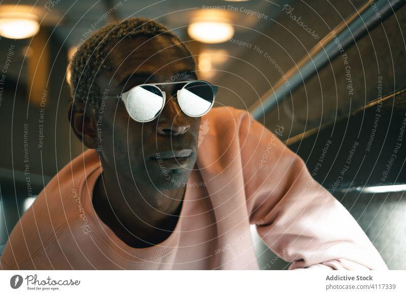 Trendiger schwarzer Mann in beleuchtetem Gang Stil Stollen modern urban leuchten ethnisch selbstbewusst Outfit fettarm männlich Wand Sonnenbrille Sweatshirt
