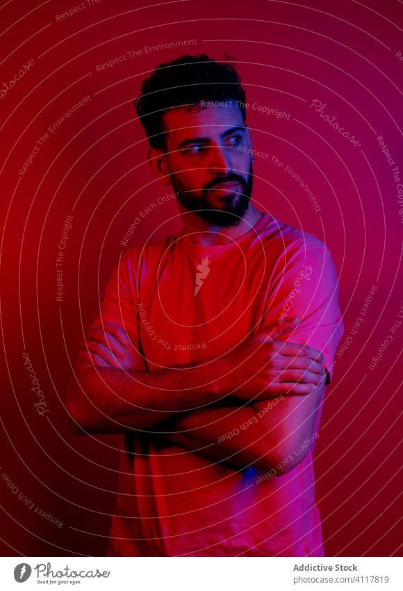 Selbstbewusster bärtiger Mann unter rotem Licht modern Stil ernst selbstbewusst die Arme verschränkt Vollbart Rotlicht hell Outfit männlich trendy T-Shirt