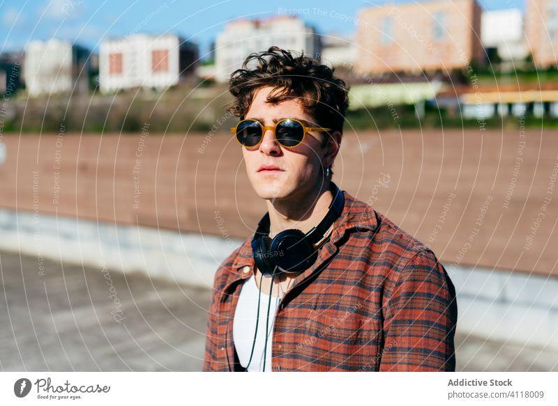 Stylischer Typ auf der Straße in der Stadt Mann Stil urban Hipster Großstadt jung Outfit selbstbewusst modern männlich Sonnenbrille kariertes Hemd Kopfhörer