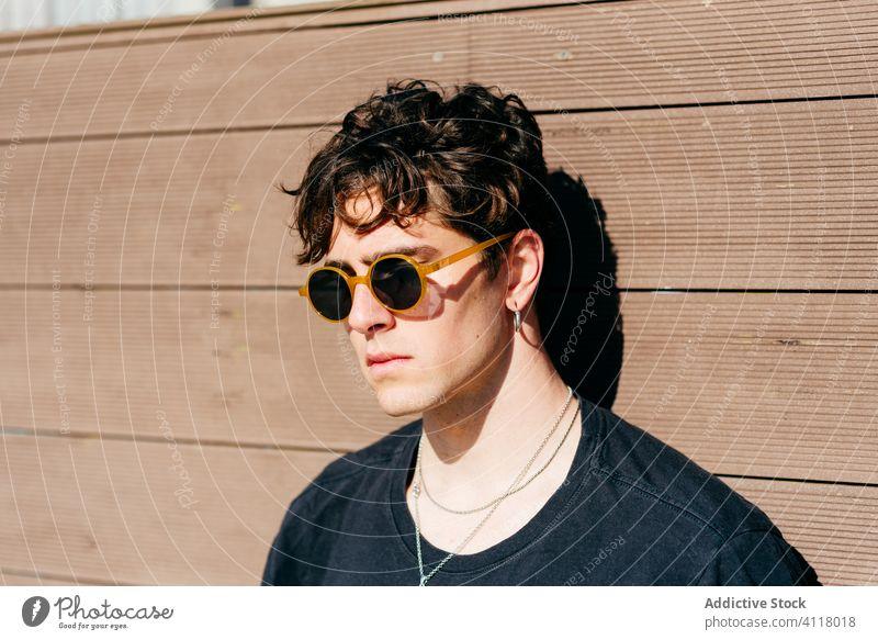 Stilvoller Mann an der Wand stehend Straße modern urban jung Großstadt Sonnenbrille schwarzes T-Shirt männlich trendy Model Hipster sonnig Gebäude Konstruktion