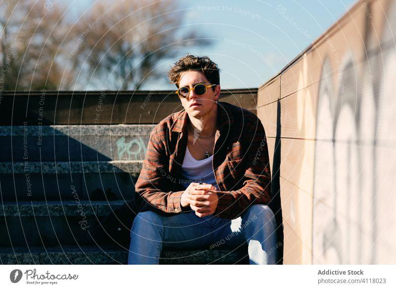 Auf Stufen ruhender junger Mann Schritt sitzen Straße urban Großstadt modern Hipster männlich sonnig Stil lässig tausendjährig trendy Stadt Lifestyle