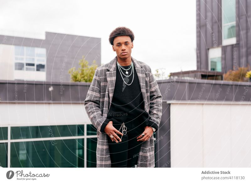 Selbstbewusster junger Mann in modischem Mantel auf der Straße Stil trendy Mode urban cool Model Großstadt Gebäude Herbst ernst modern Afroamerikaner schwarz