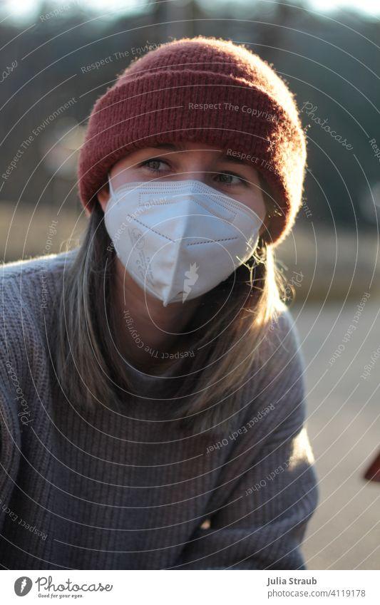 Junge Frau mit Mütze und FFP2  Atemschutzmaske sitz im Abendlicht Maske Maskenpflicht ffp2-maske ffp2 Schutzmaske coronakrise Corona-Pandemie Strickpullover