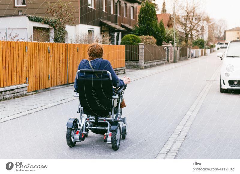 Frau fährt mit einem elektrischen Rollstuhl auf der Straße. Menschen mit Behinderung und Mobilität. Elektrorollstuhl elektrischer Rollstuhl mobil behindert