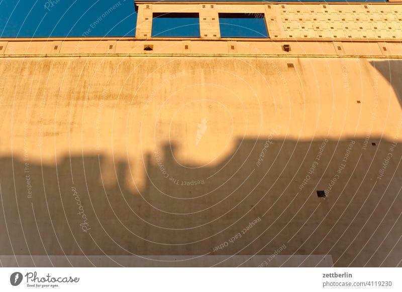 Fassade mit dem Schatten einer anderen Fassade altbau außen brandmauer fassade fenster haus himmel himmelblau hinterhaus hinterhof innenhof innenstadt
