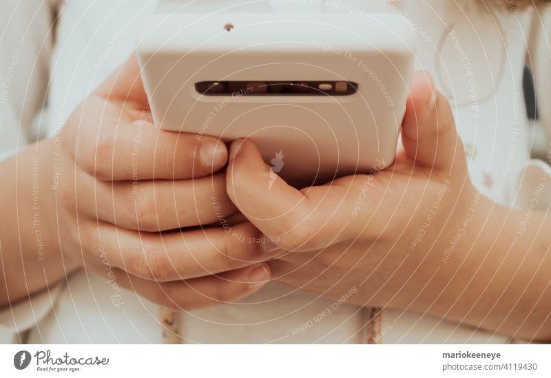 Nahaufnahme eines Smartphones und der Hände eines kleinen Mädchens kleines Mädchen detaillierte Ansicht Technik & Technologie Beteiligung benutzend Sucht