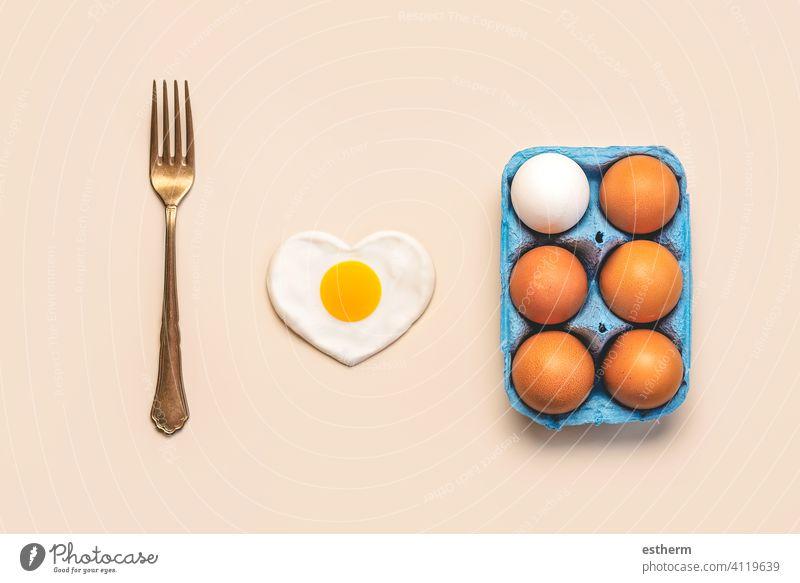 Draufsicht auf Hühnereier in einer offenen blauen Pappschachtel mit einer Vintage-Gabel und einem herzförmigen Spiegelei Eier Ostereier Hähnchen frisch Eigelb