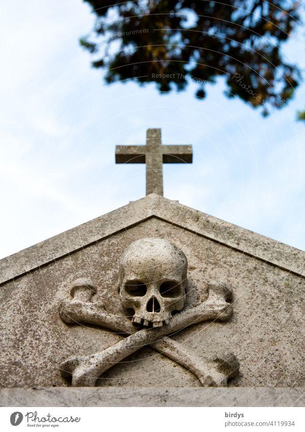 christliches Kreuz mit einem Totenkopf darunter auf einem Friedhof , Froschperspektive Tod sterben Christliches Kreuz Grab Religion & Glaube symbolik