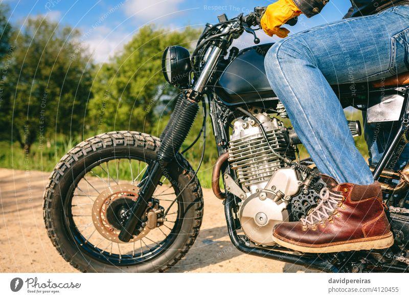 Mann auf einem Custom-Motorrad unkenntlich Reiten benutzerdefiniert Profil altehrwürdig Handschuhe Beteiligung packend Lenker gestoppt Fahrrad cool erbaut