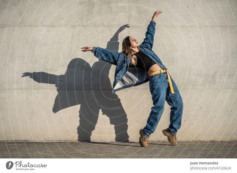Tänzerin Frau macht eine Pose wie ein Adler. Casual Kleid und Schatten an der Wand reflektiert. mögen lässig Textfreiraum Kopierbereich copyspace Gleichgewicht