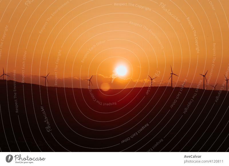 Silhouetten von einigen Windmühlen auf der Spitze eines Berges während einer super orange Sonnenuntergang mit Kopie Raum friedlich Pflanze Energie regenerativ