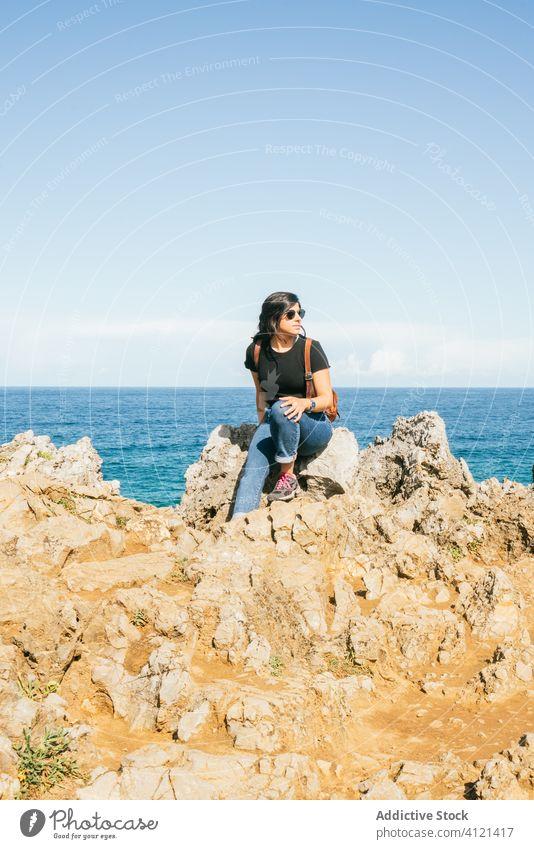 Junge Frau sitzt auf einer Klippe am Meer Meeresufer Strand MEER Harmonie erstaunlich Windstille Himmel Ansicht idyllisch Felsen reisen schön Sonnenbrille Natur