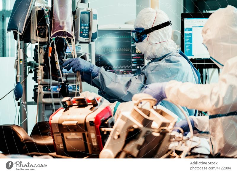 Innenraum eines Krankenwagens mit Ärzten im Schutzanzug Arzt Menschengruppe Uniform Gerät geduldig Dienst PKW Krankenhaus Klinik professionell Arbeit Fahrzeug