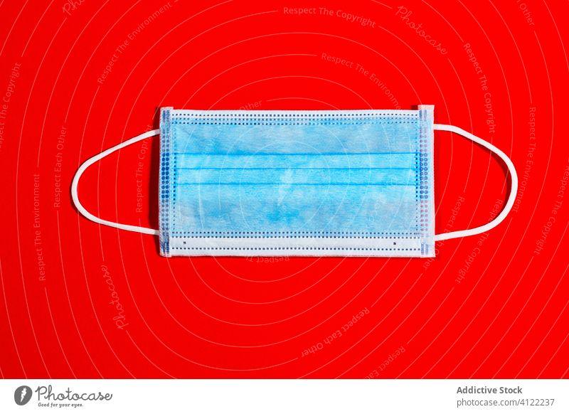 blaue Einwegmaske zum Schutz vor Viren auf rotem Hintergrund Coronavirus Seuche Gesundheit Quarantäne Infektion Krankenhaus Virus Pandemie medizinisch Krankheit