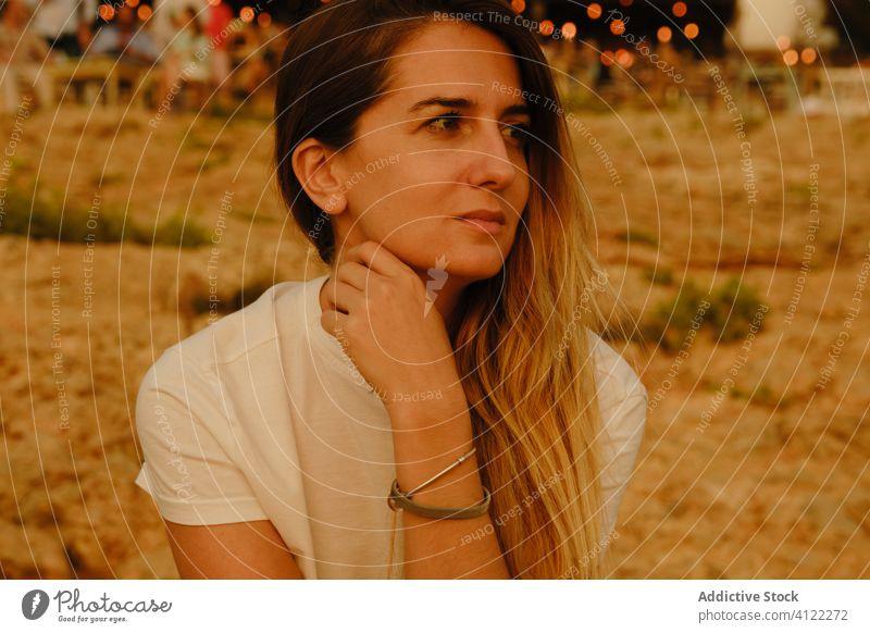 Junge Touristin ruht sich abends an der Strandpromenade aus Frau Stein Sonnenuntergang Meeresufer träumen Inspiration beobachten Ibiza Spanien Küste