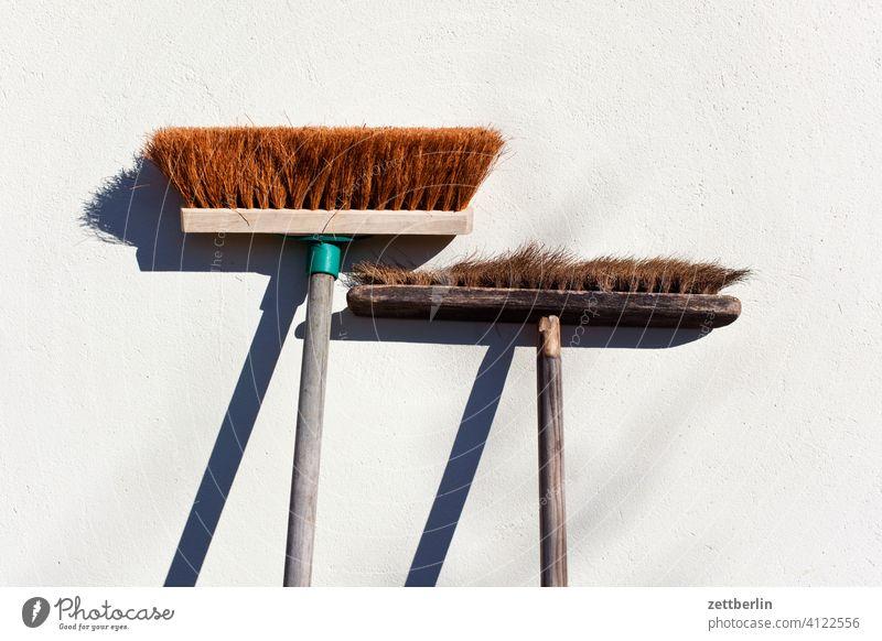 Zwei Besen alt alter angelehnt anlehnen besen borsten eltern entwicklung generation kontrast licht neu paar pause schatten stehen straßenbesen stubenbesen zwei