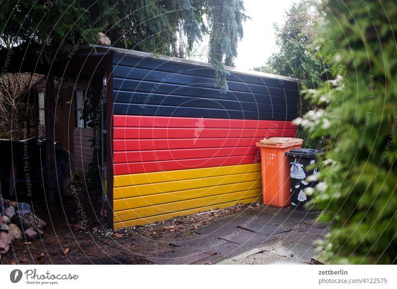Deutsche Nationalfarben an der Schuppenwand deutschland deutschlandfahne frühjahr frühling garage garten gold kleingarten kleingartenkolonie menschenleer