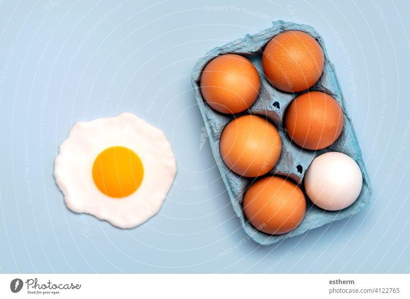 Draufsicht auf Hühnereier in einer offenen blauen Pappschachtel und ein Spiegelei Eier Ostereier Hähnchen frisch Eigelb essen Container Korb Landwirtschaft