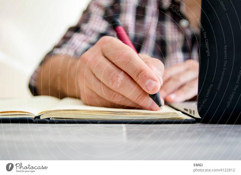Ein Mann schreibt in ein Notebook neben einem Laptop E-Learning Person Bildung Computer Lernen online Business heimwärts Technik & Technologie studierend