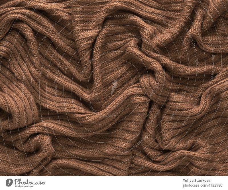 Brown zerknittert gestrickten Schal oder Pullover Textur, Ansicht von oben. Textur Hintergrund der warmen gehäkelte Kleidung Textil. Strickwaren Stoff. stricken