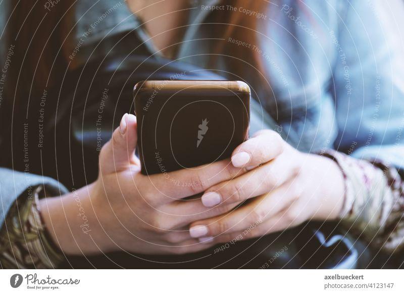 Hände einer nicht erkennbaren jungen Frau, die ein Smartphone oder Mobiltelefon benutzt Handy benutzen Telefon benutzend Technik & Technologie Texten digital