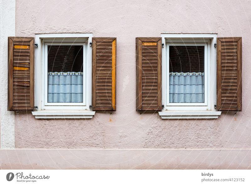 Fassade mit 2 Fenstern und kaputten Klappläden aus Holz. verlassenes Haus in Keyenberg / NRW , das Dorf soll von RWE vernichtet werden um an klimaschädliche Braunkohle zu kommen