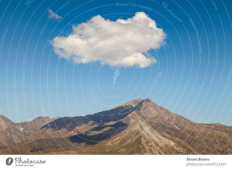 Landschaftsfotografie von steilen Bergen im Sommer, einsamen Wolken und stillen Hochweiden, in den aragonesischen Pyrenäen, Provinz Huesca, im Gebiet des Naturparks Posets-Maladeta.