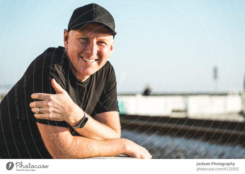 Outdoor-Porträt eines lächelnden Mannes in den 40ern im Freien positiv Lächeln sonnig Verschlussdeckel Jockeymütze in die Kamera schauen Textfreiraum Freude