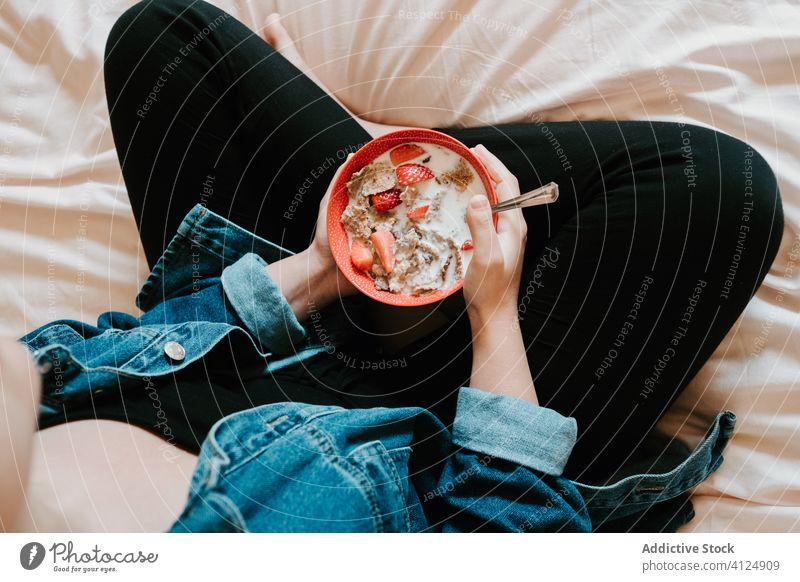 Frau isst zu Hause eine Milchmischung aus Erdbeeren und Haferflocken melken essen Hand Schalen & Schüsseln Lebensmittel Diät Gesundheit Beeren rot Molkerei