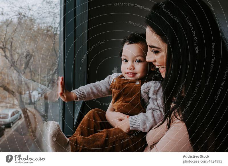 Positive junge Mutter und kleiner Sohn stehen am Fenster und bewundern die Aussicht heimwärts neugierig erkunden Punkt Ansicht Inhalt aufgeregt niedlich wenig