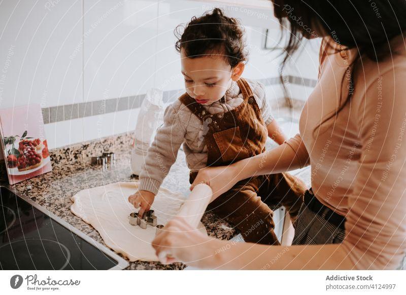 Fröhlicher kleiner Junge beim Backen von Gebäck mit seiner Mutter in der Küche Koch Helfer Teigwaren Bonden heiter Lebensmittel Eltern Assistent Lächeln