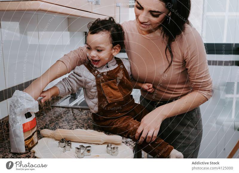 Fröhliche Mutter beim Backen von Gebäck mit kleinem Sohn in der Küche Koch Nudelholz Teigwaren Keks Helfer Assistent Zusammensein Bonden Liebe Stuhl Kind heiter