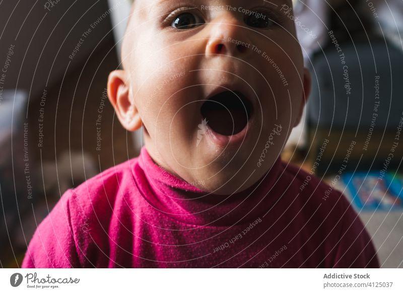 Lustiger kleiner Junge sitzt zu Hause und schaut in die Kamera heimwärts erstaunt wow sprachlos Mund geöffnet spielen heiter niedlich Stock omg charmant