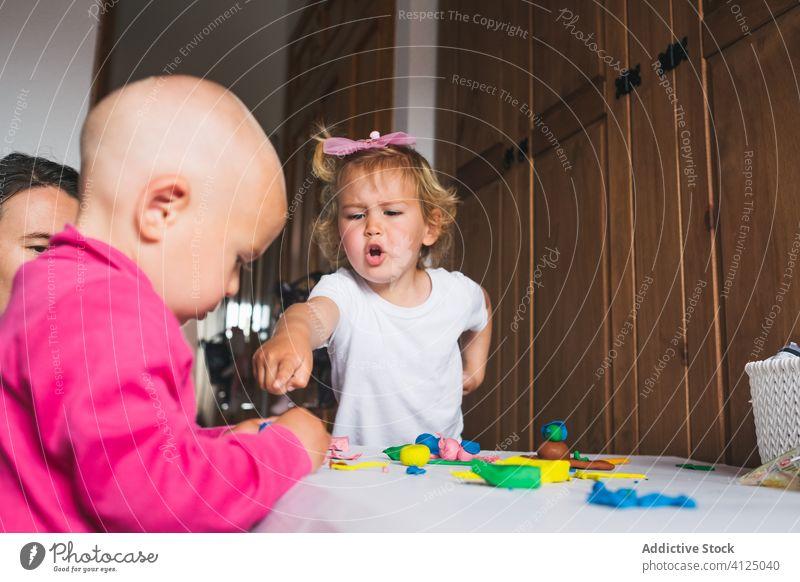 Fröhliche Geschwister, die zu Hause mit Knetmasse spielen Kinder Geschwisterkind Modellierung Ton farbenfroh Mutter Erziehung Entwicklung Vorschule heimwärts