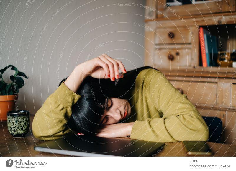 Eine Frau schläft zuhause am Tisch vor ihrem zugeklapptem Laptop Arbeit schlafen Home Office langweilig müde Mittagsschlaf Homeoffice Notebook erschöpft