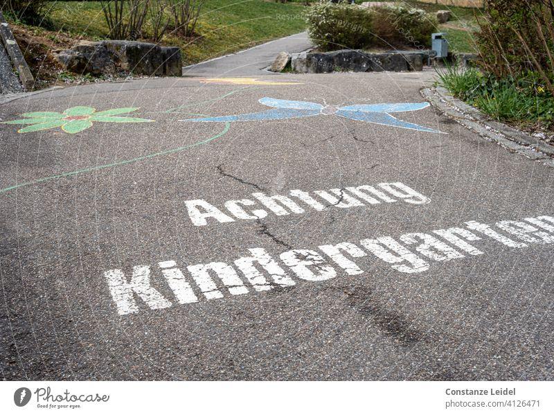 Straßenbemalung Achtung Kindergarten Straßenverkehr Kreidezeichnung Straßenkunst Vorsicht gefährlich Farbfoto Außenaufnahme Schilder & Markierungen Warnhinweis