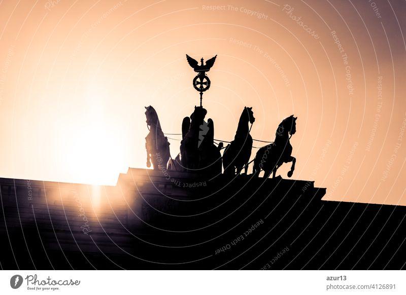 Brandenburger Tor mit Quadriga in Berlin - Hauptstadt von Deutschland in Europa. Sonnenuntergang hinter dem deutschen Symbol und europäischen Wahrzeichen am Pariser Platz. Highlight jeder Sightseeing Tourismus Tour über deutsche Geschichte.