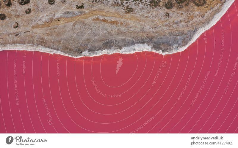 Aerial Drohne von oben nach unten Foto von einem natürlichen rosa See und Küste Genichesk, Ukraine. See wird natürlich rosa durch Salze und kleine Krebstiere Artemia im Wasser. Dieses Wunder ist selten.