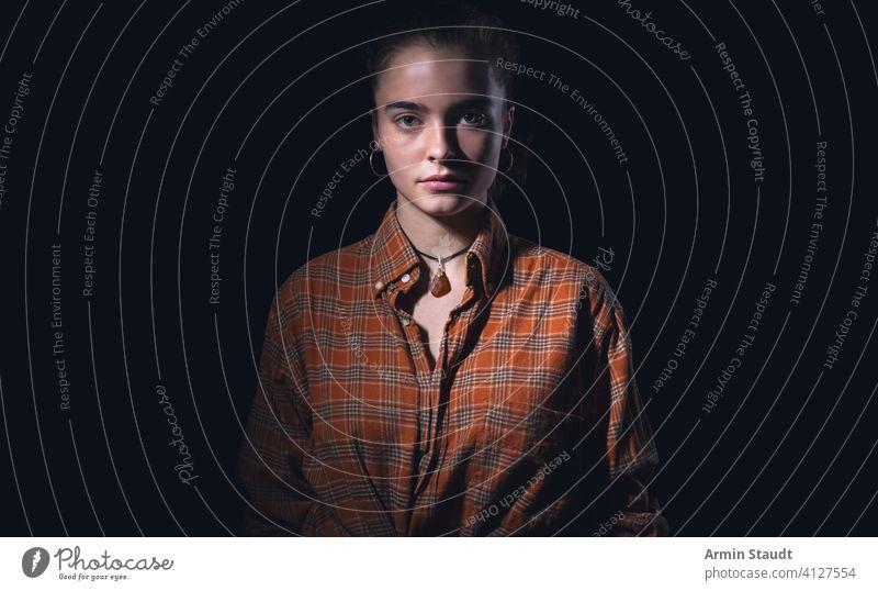 Porträt einer schönen Teenagerin mit orangefarbenem kariertem Hemd Frau Stehen Atelier ernst geheimnisvoll menschlich schwarz vereinzelt kampfstark