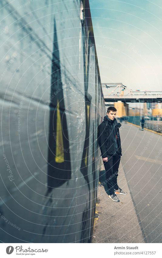 Porträt eines traurigen jungen Mannes, der an einer Wand lehnt Lehnen Silber im Freien beunruhigt müde Stehen Perspektive abnehmend Brücke Eisenbahn Jogger