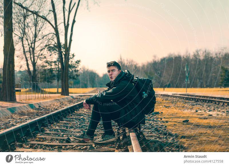 glücklicher junger Mann mit Rucksack auf Bahngleisen sitzend Sitzen Eisenbahn Spuren Landschaft im Freien Lächeln selbstbewusst kampfstark weit weg Wald Natur