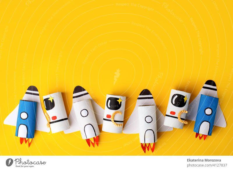 Schule Kindergarten Handwerk, Papier Raumschiff, Shuttle, Astronaut auf gelbem Hintergrund mit Kopie Raum für Text. Party, Start-up Startkonzept, diy, kreative Idee aus Toilettenschlauch, recyceln