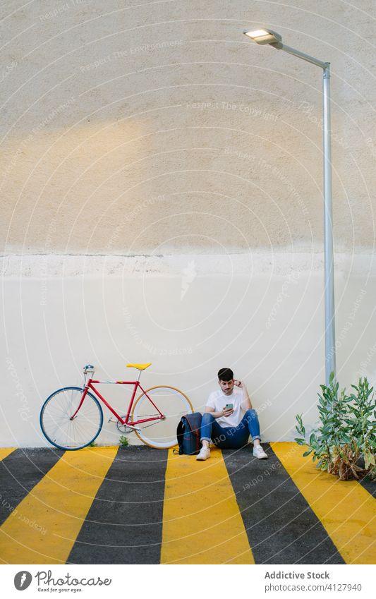 Mann auf dem Boden sitzend mit einem Fahrrad Fixie Zyklus urban Rad feststehend Sport Transport Ausrüstung Lifestyle Wand Straße Hipster Mitfahrgelegenheit