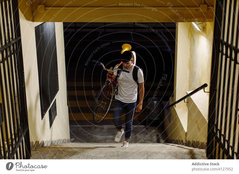 Mann steigt eine Treppe hinauf und hält ein Fahrrad Fixie Zyklus urban Rad feststehend Sport Transport Ausrüstung Lifestyle Wand Straße Hipster